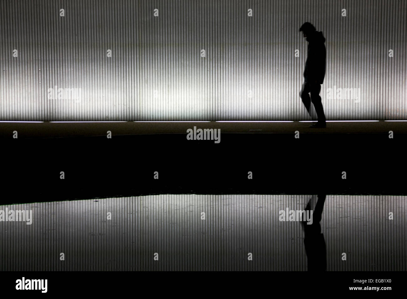 Lonely man walking under a bridge/tunnel Stock Photo