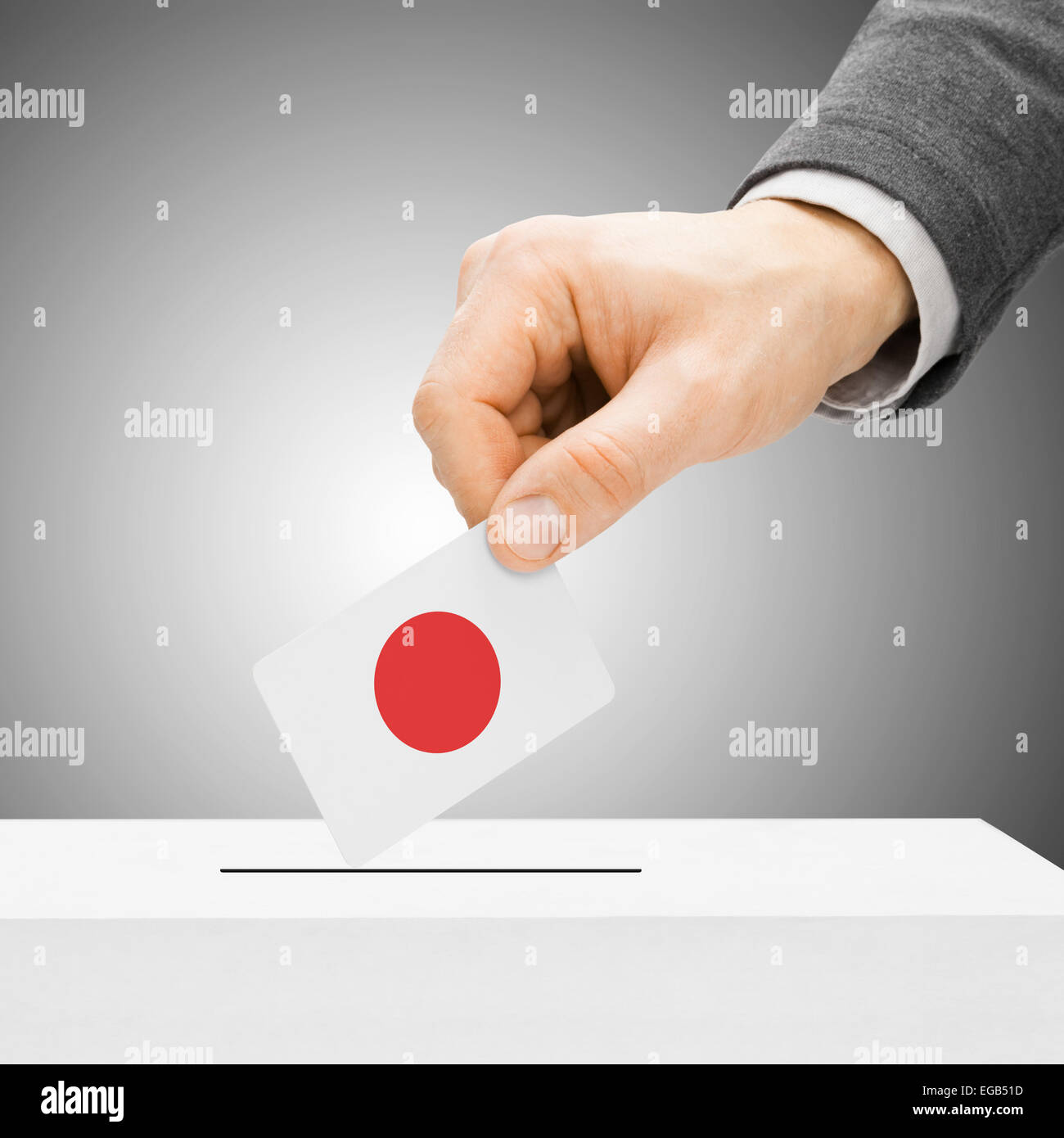 Voting concept - Male inserting flag into ballot box - Japan Stock Photo