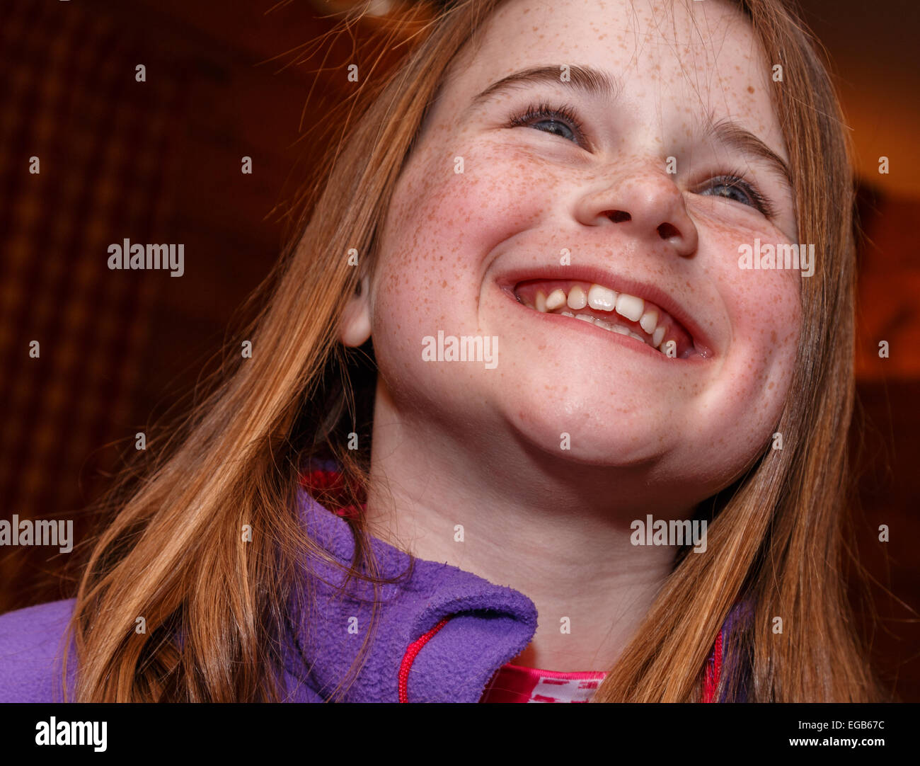 Smiling girl with red hair and freckles.  Big grin. Shot from below underneath. - Stock Image