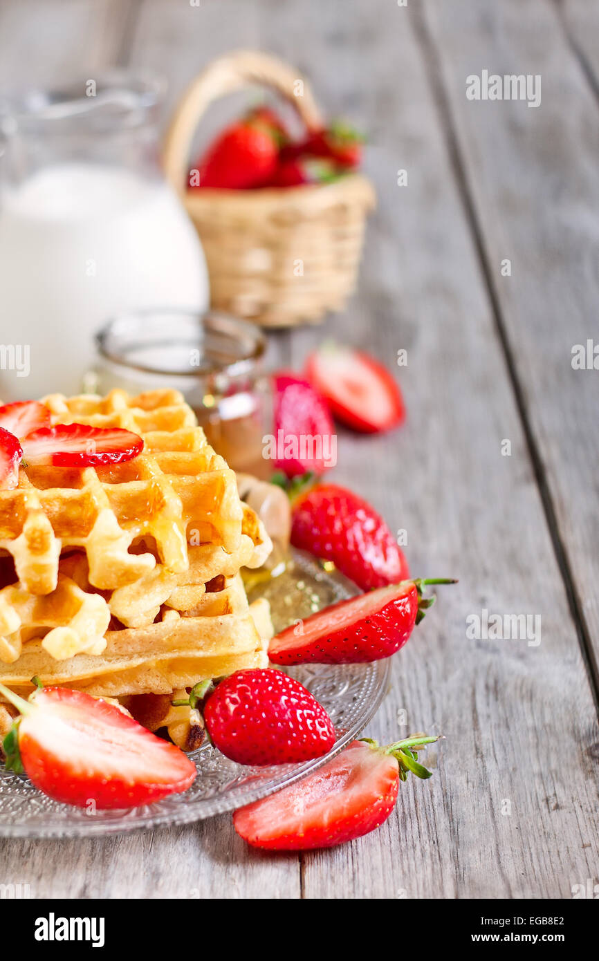 Homemade belgian waffles with ripe strawberry, honey and milk on wooden background Stock Photo
