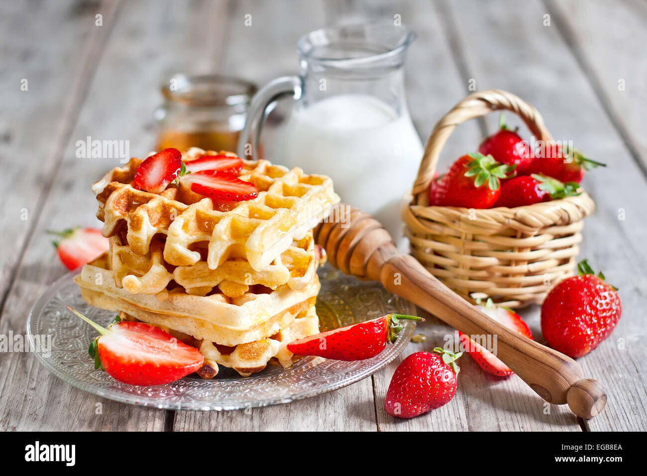 Homemade belgian waffles with ripe strawberry, honey and milk on wooden background - Stock Image