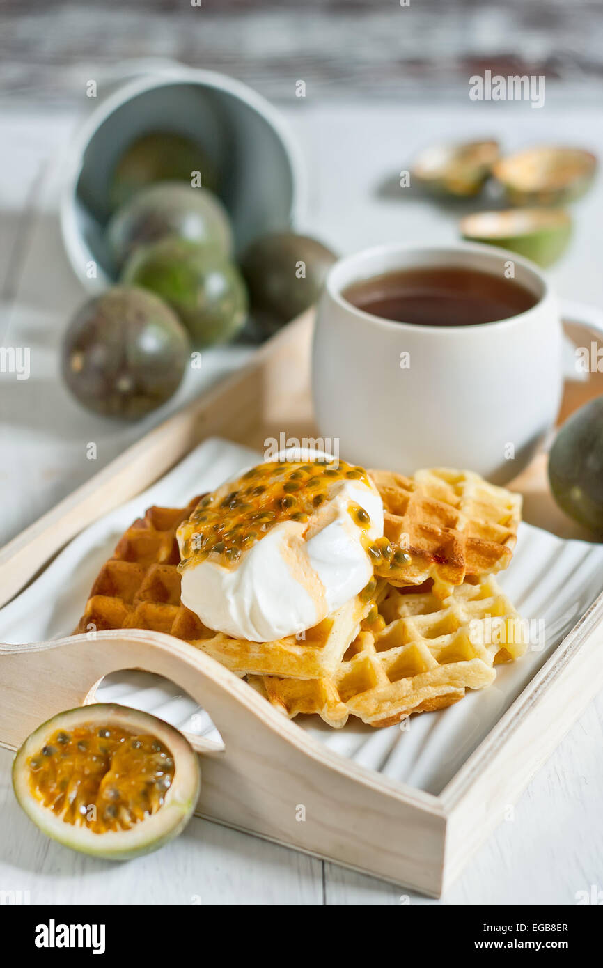 Homemade belgian waffles with cream and passionfruit pulp. Selective focus. - Stock Image