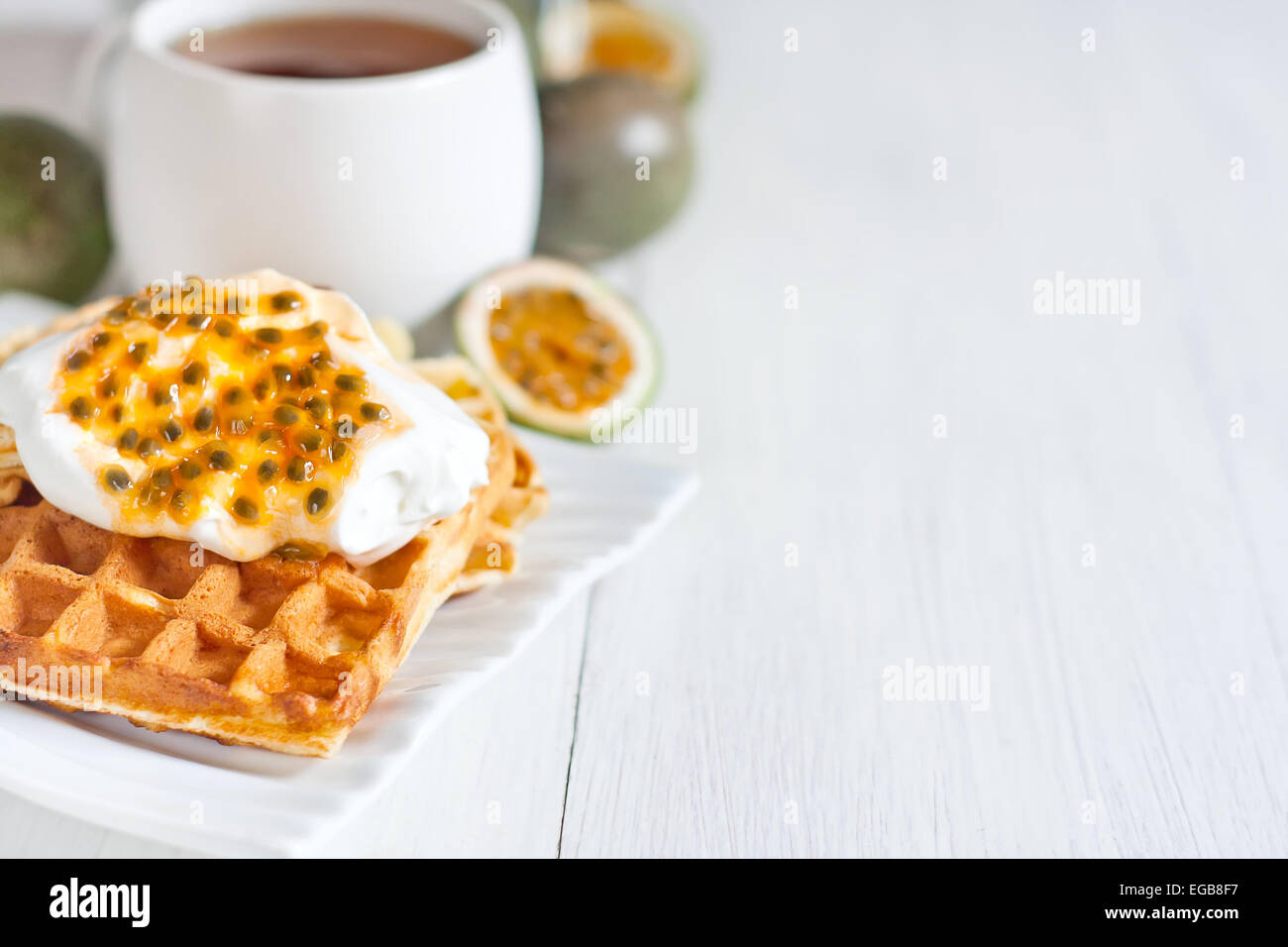Homemade belgian waffles with cream and passionfruit pulp. Selective focus. Copyspace background. - Stock Image