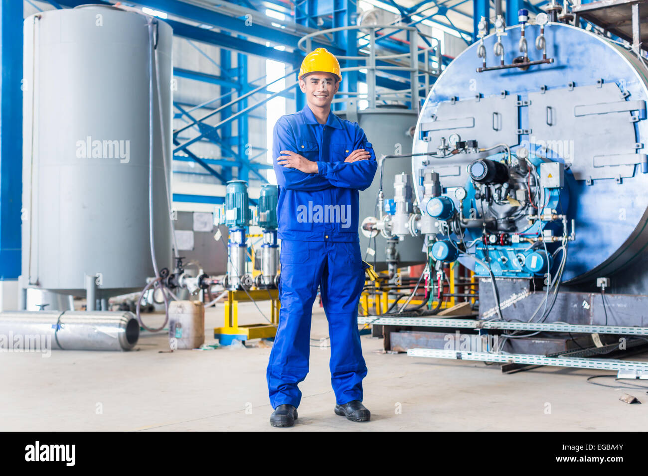 Proud Asian worker standing in production factory Stock Photo
