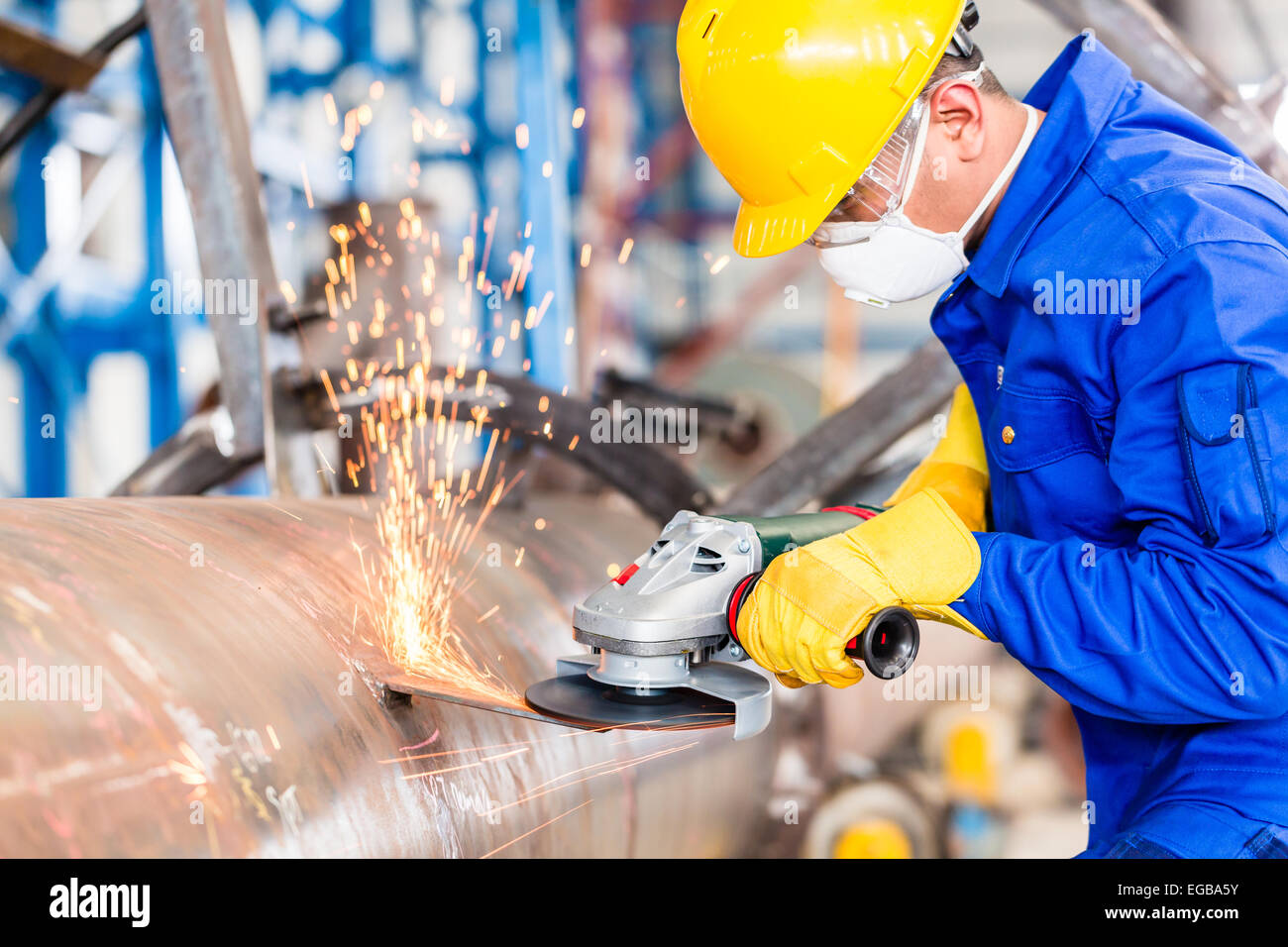 Industrial worker in manufacturing plant grinding to finish a pipeline - Stock Image