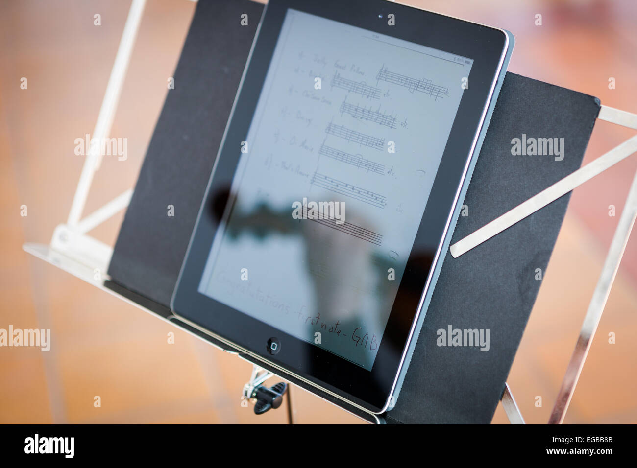 Reflection on a ipad of violinist with his violin playing during a wedding whilst reading digital sheet music - Stock Image