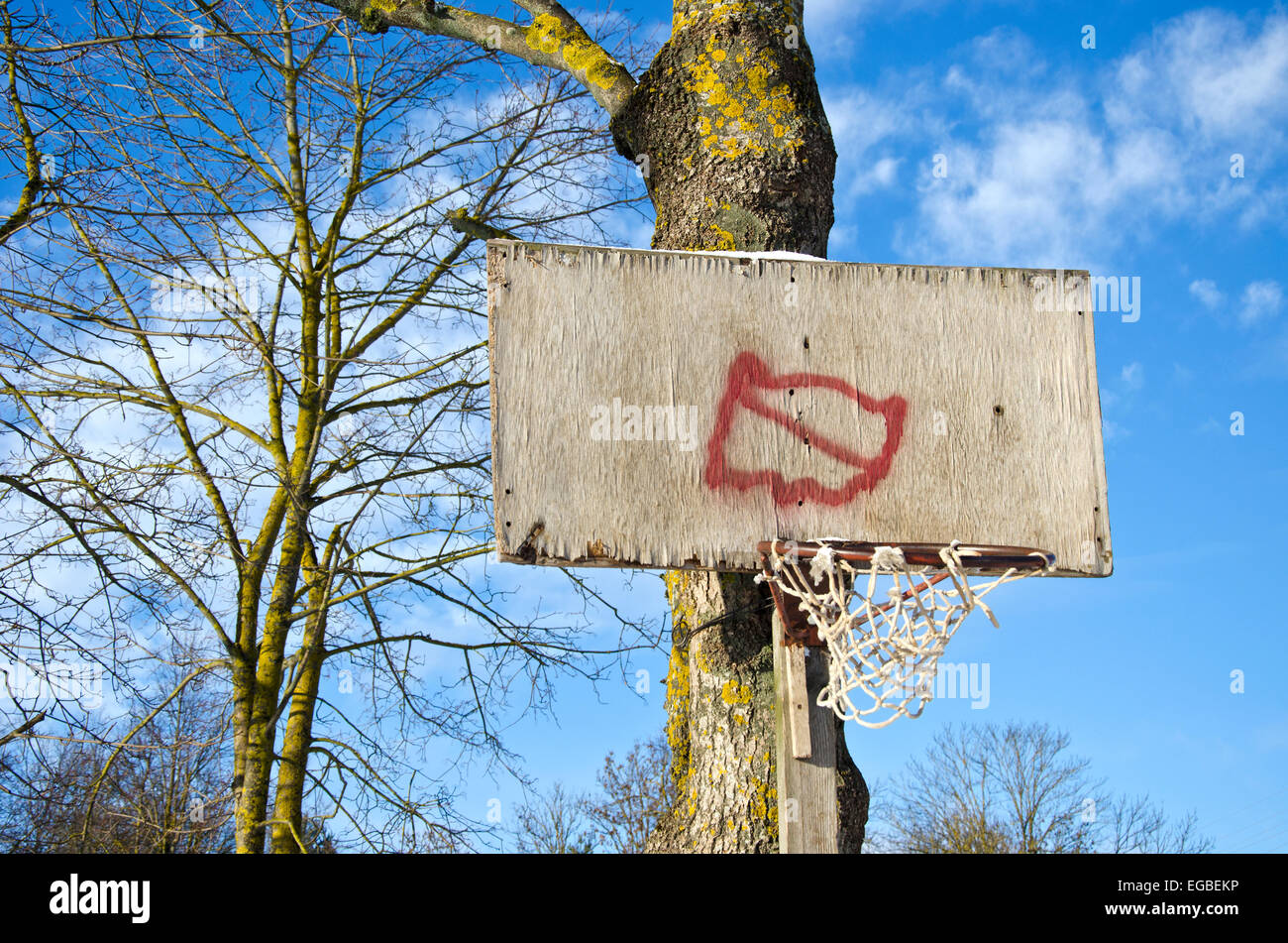 Basketball hoop primitive board with broken net on tree in city park - Stock Image