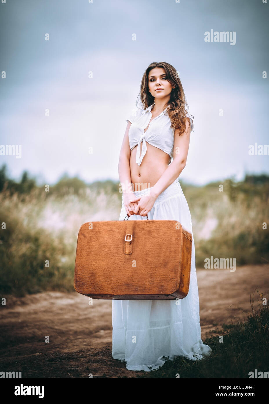 Beautiful young woman with suitcase in hands stands on a field road - Stock Image
