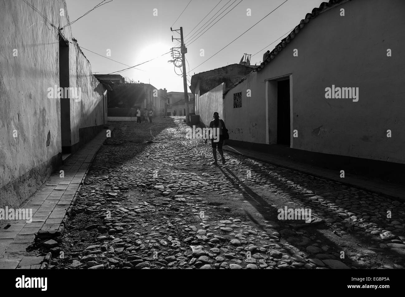 A shadowy figure walking up a cobbled street in Trinidad, Cuba. - Stock Image