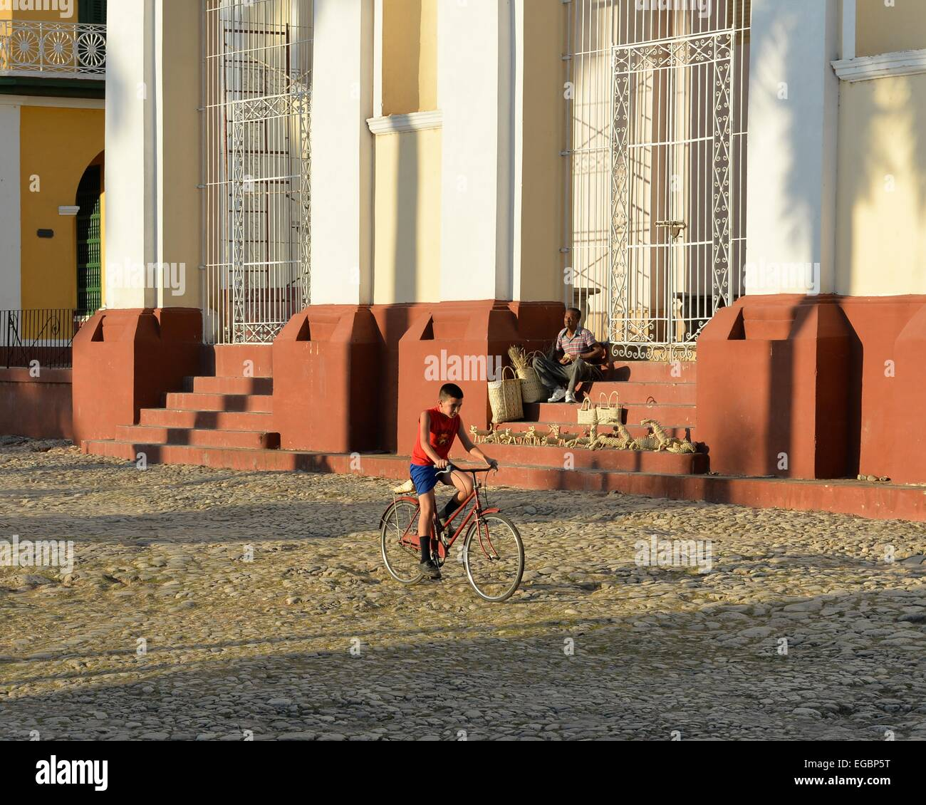Iglesia Parroquial de la Santisima Trinidad in La Plaza Mayor, with a boy riding a bike and a man sat on the steps. - Stock Image