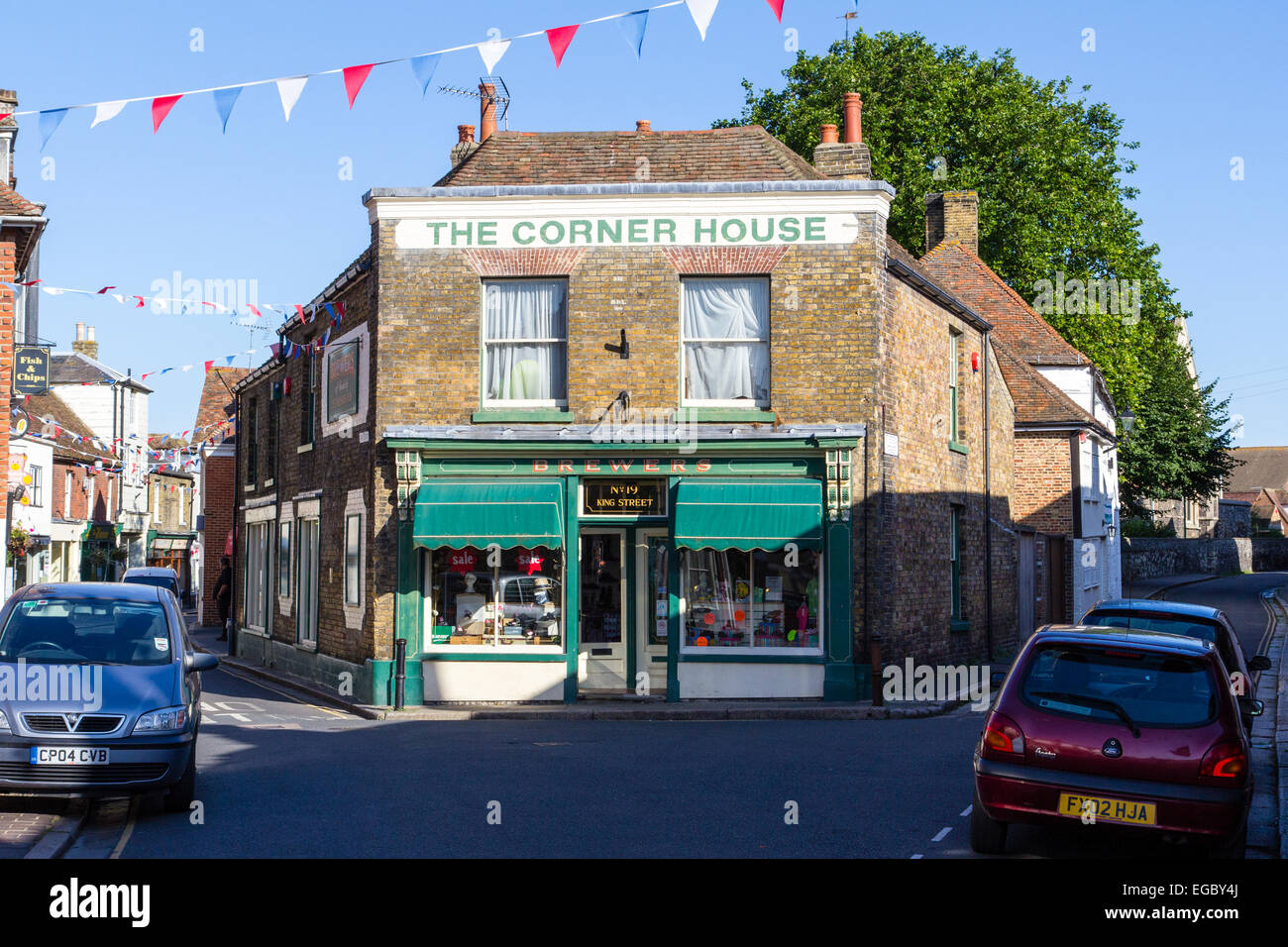 England, Sandwich. 19th century shop, 'The Corner House' Double fronted brick building at apex of two merging - Stock Image