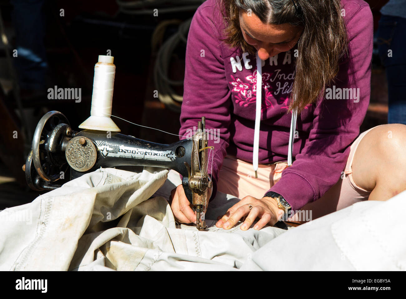 England, Ramsgate. Replica Russian 1703 Frigate, Shtandart. Teenage woman sewing sails on deck with old Russian - Stock Image