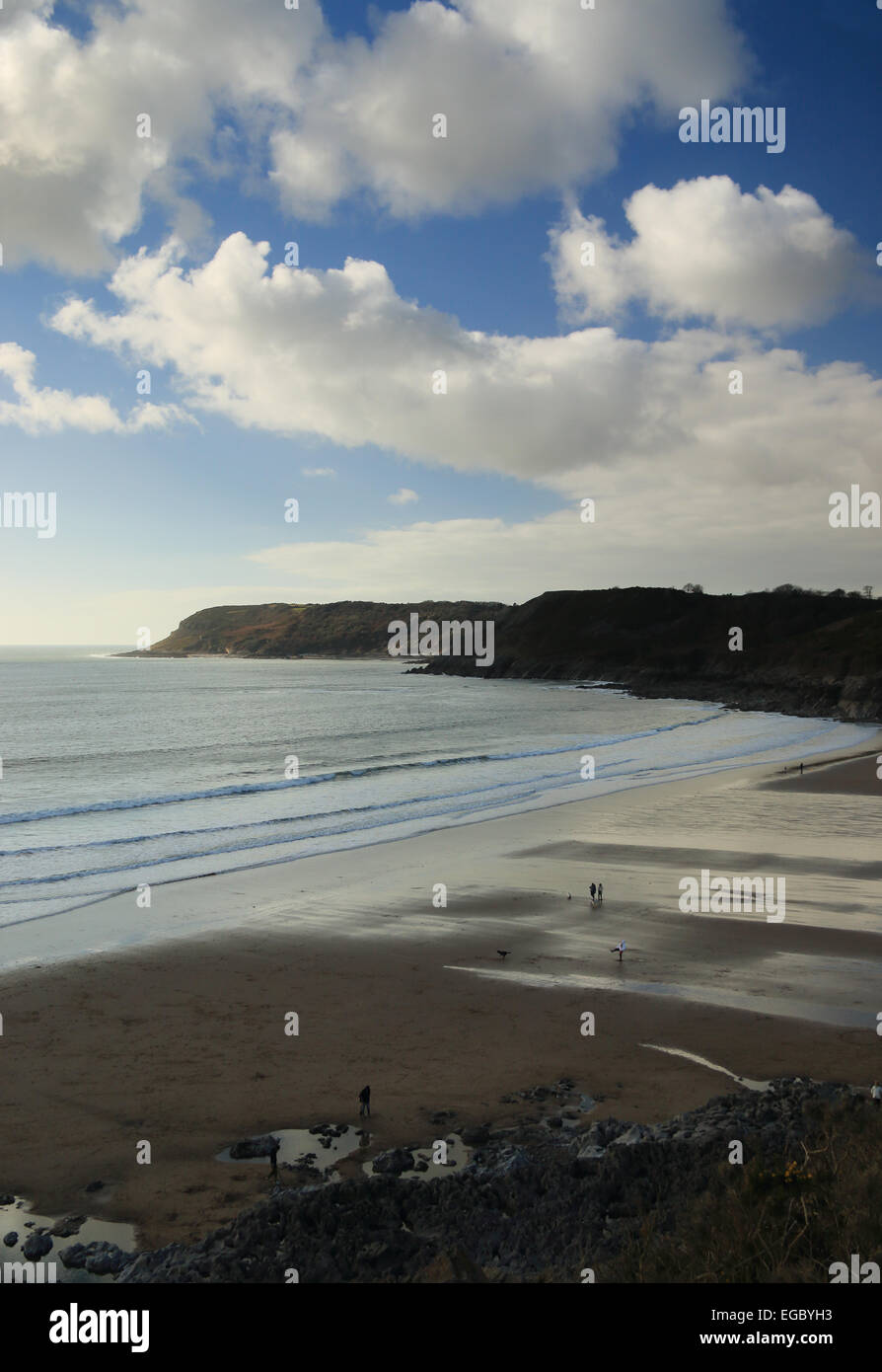 Tide receding and family walking on beach Caswell Bay Gower South Wales UK Stock Photo