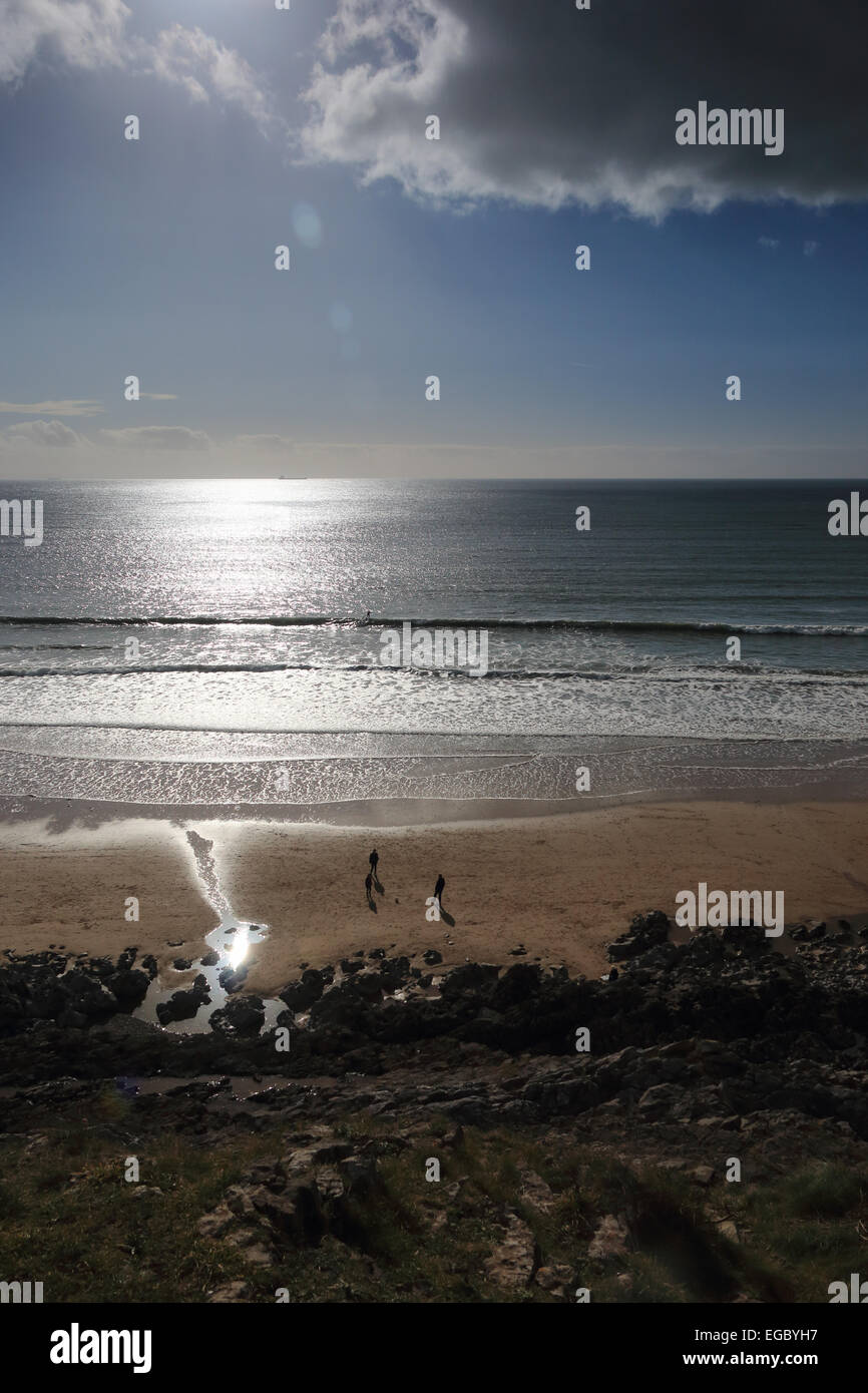 Sun reflecting on sea people playing on beach Caswell Bay Gower South Wales UK Stock Photo