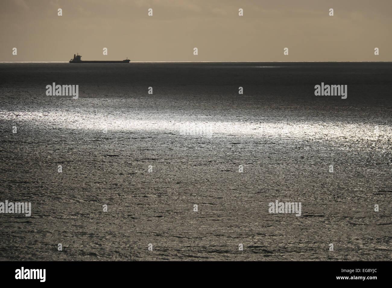 Oil tanker on horizon of sunlit sea - Stock Image