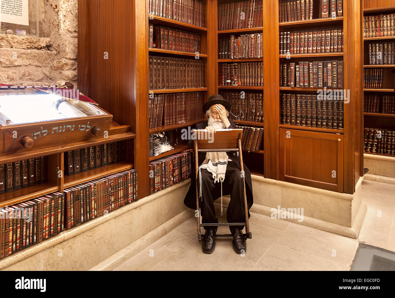 Old rabbi learns Torah among wooden bookshelves with holy books in Cave Synagogue, Jerusalem. Stock Photo