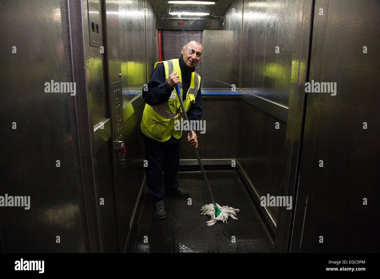 Man mopping the floor of a lift or elevator in a block of London flats - Stock Image