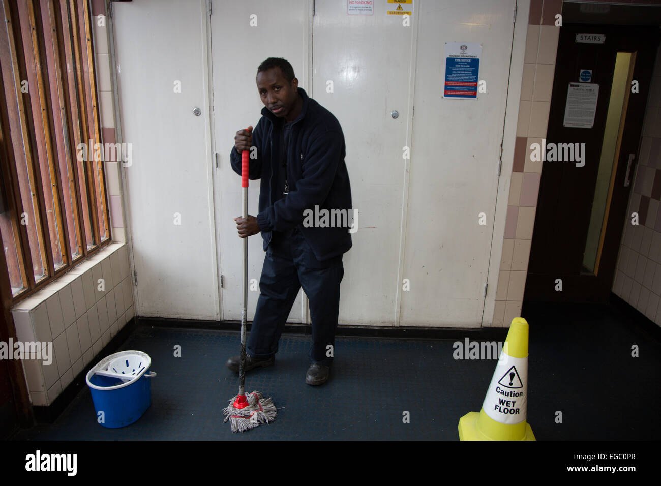 Man mopping floor in a London social housing flat - Stock Image