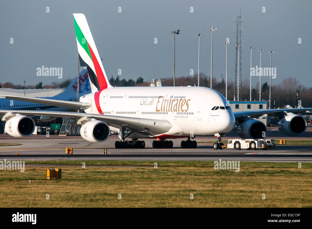 Emirates Airbus A380-800 pushes back from terminal 1 at Manchester airport. - Stock Image
