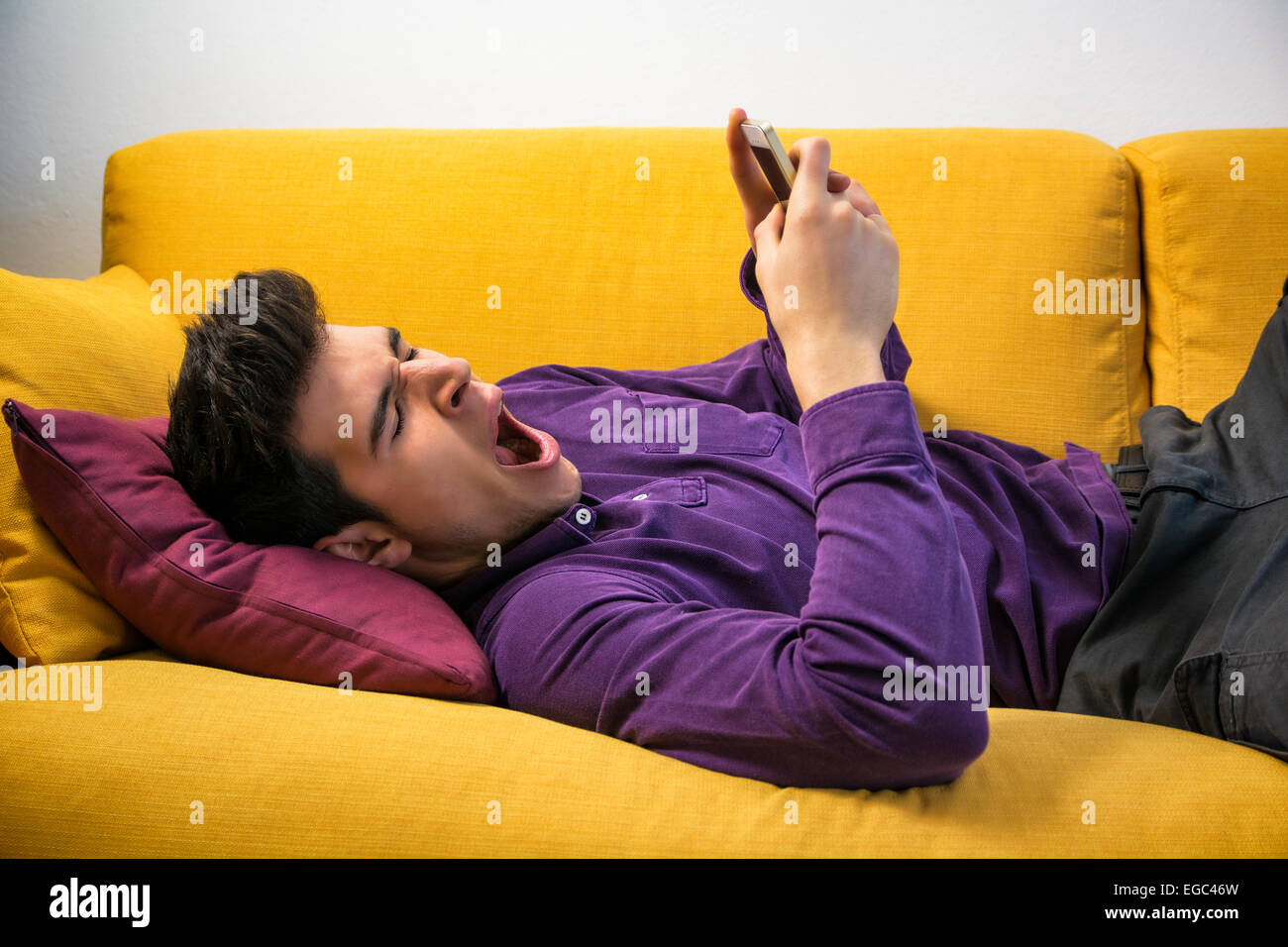 Attractive young man using cell phone and yawning, tired Stock Photo