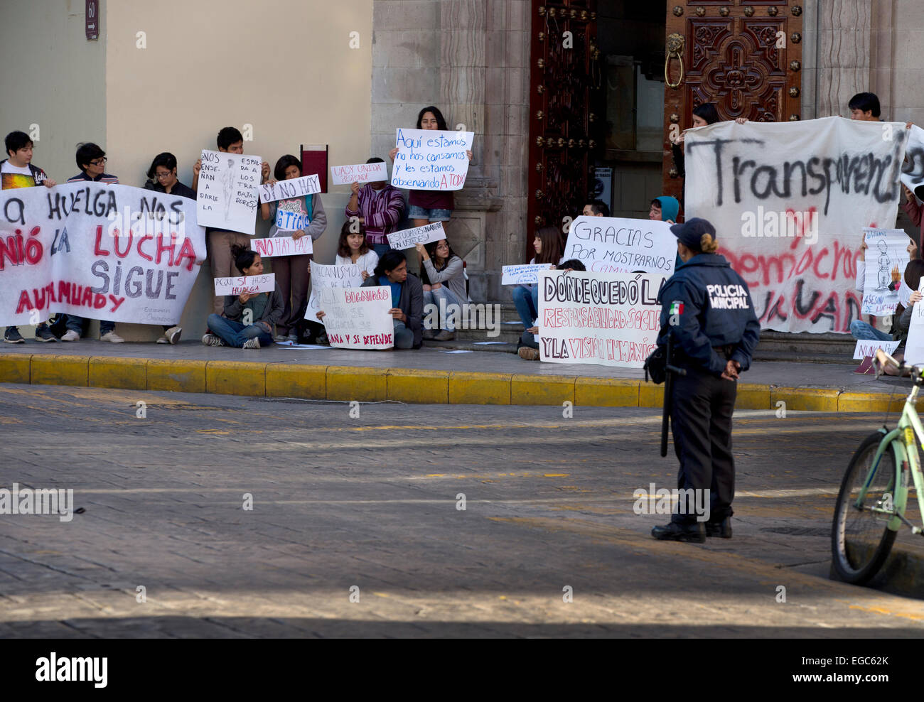 A policewoman watches over a university student demonstration, Merida, Yucatan, Mexico - Stock Image