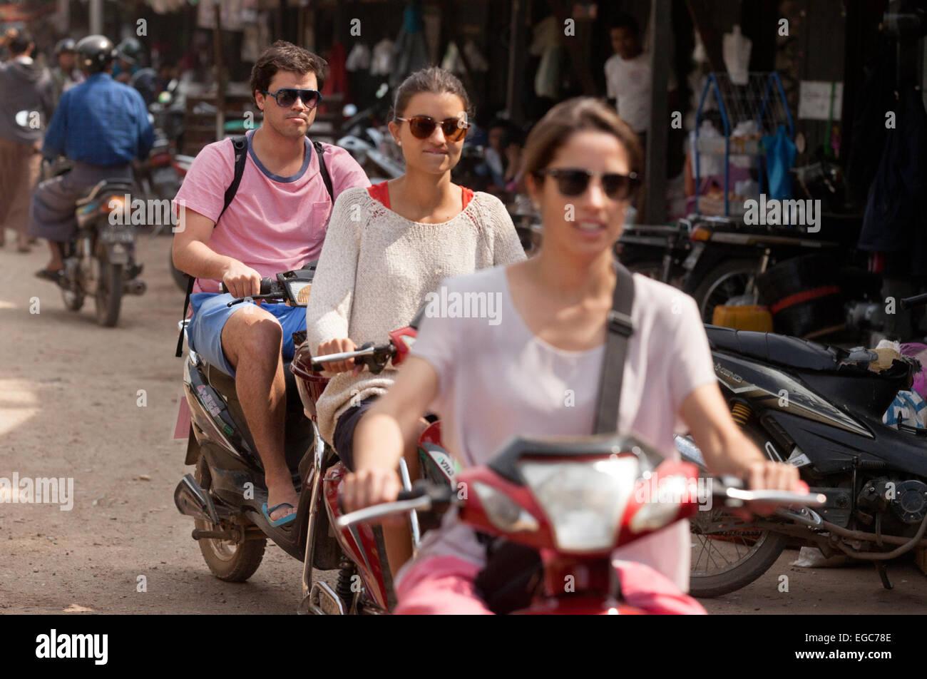 Three western tourists riding motorbikes, Bagan, Myanmar ( burma ), Asia - Stock Image