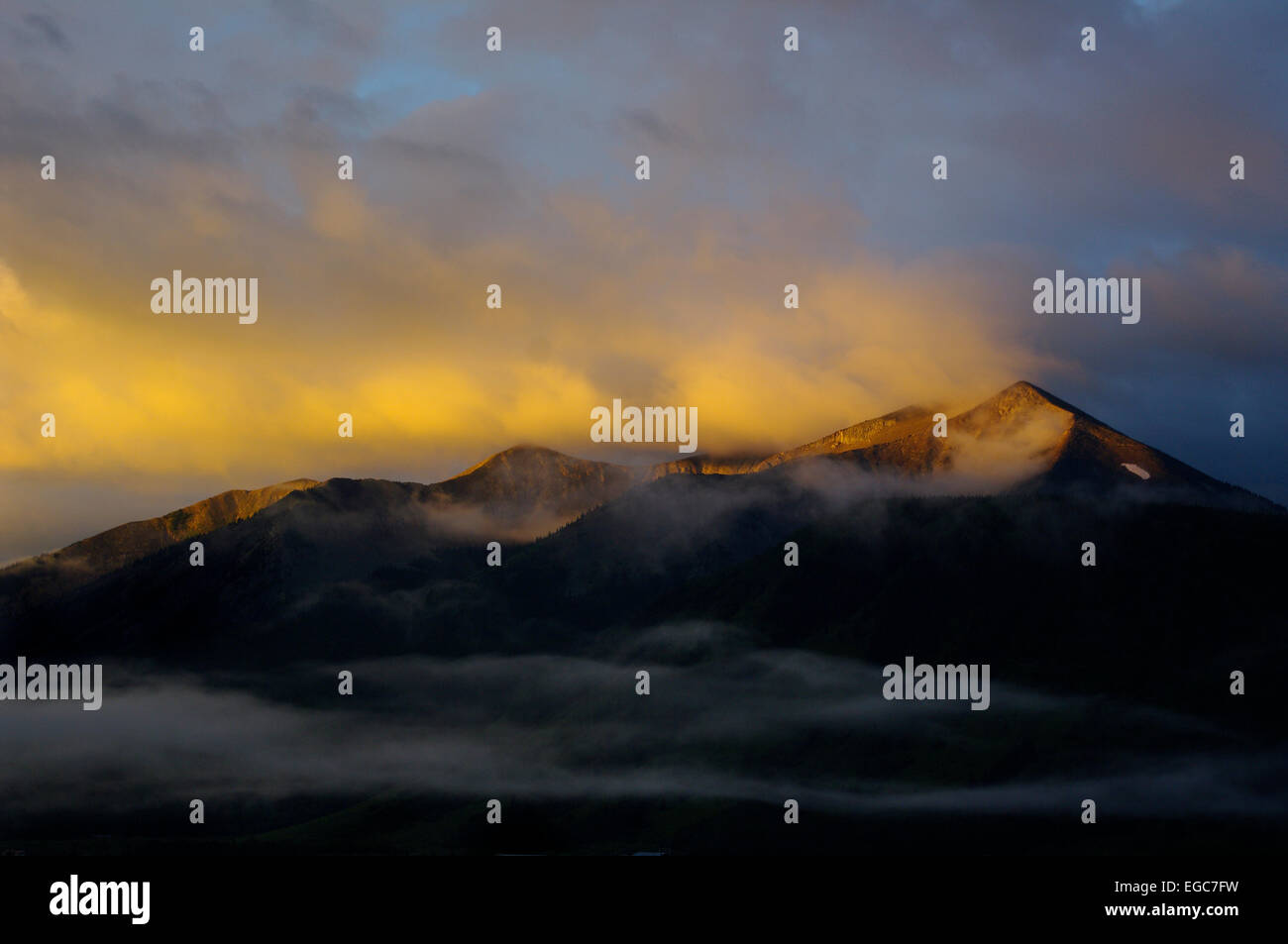 Sunrise in Crested Butte, Colorado.  Orange clouds above the Rocky Mountains on a foggy morning. - Stock Image
