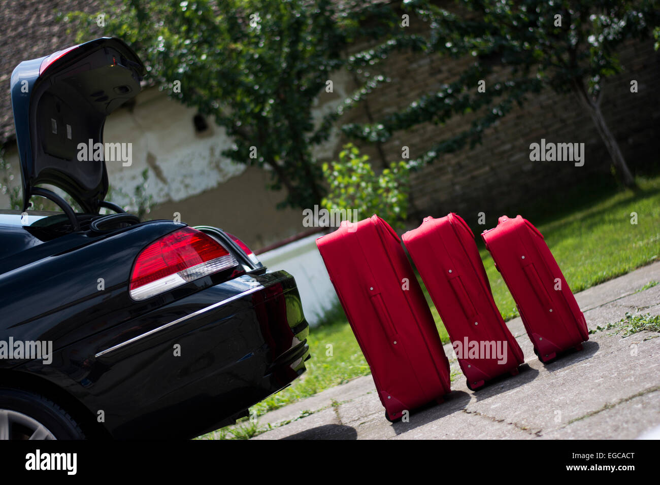 Red suitcases waiting to be packed and ready for travel - Stock Image