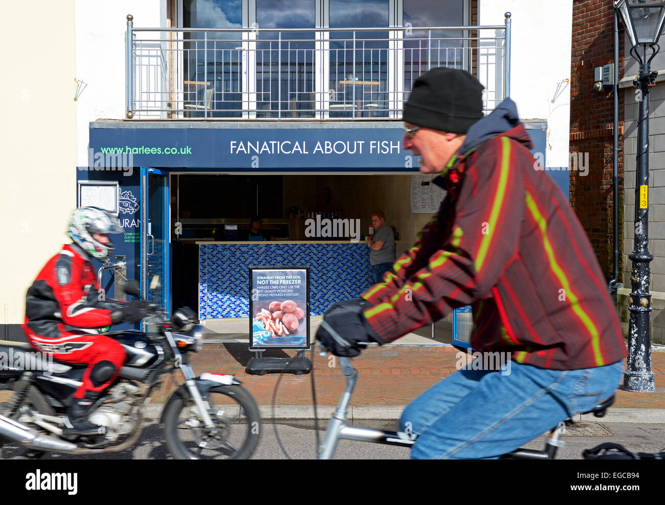 Cyclist and biker pass a fish & chip shop, Poole Dorset, England UK - Stock Image