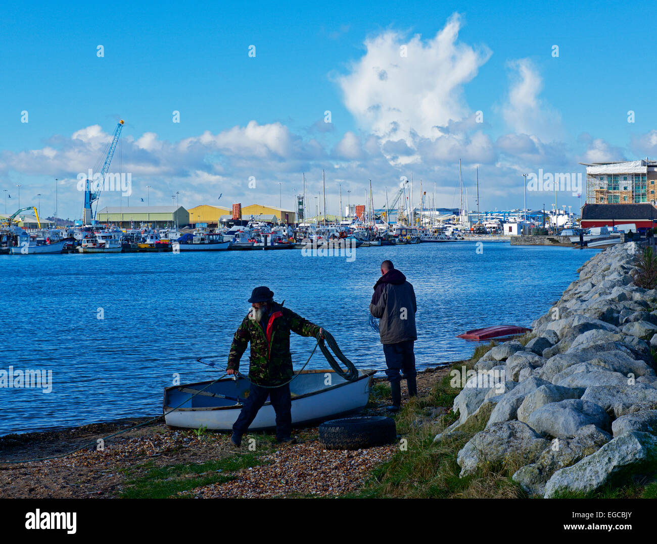 Two men and dinghy at Poole Harbour, Dorset, England UK - Stock Image