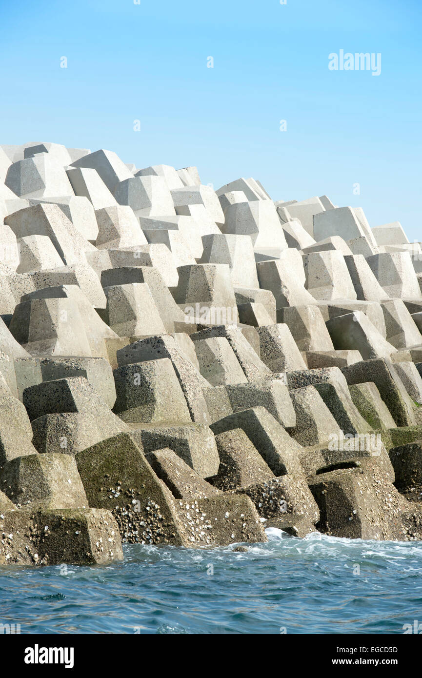 Concrete forms interlocked to make a sea wall breakwater. - Stock Image