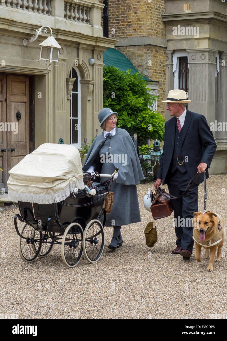 1940s re-enactment couple doctor nanny vintage pram rescue dog-PORTRAIT - Stock Image