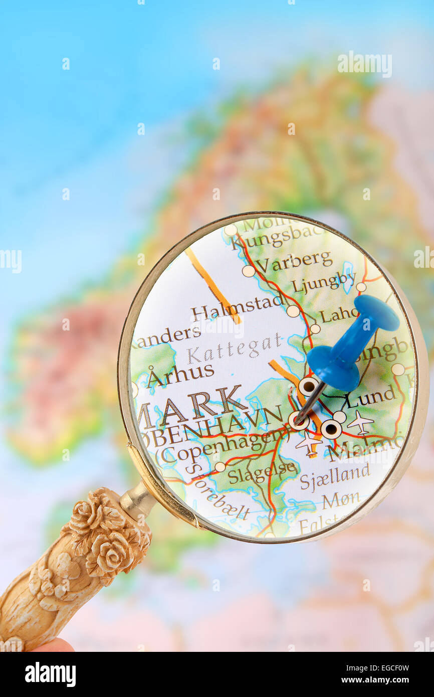 Blue tack on map of Scandinavia with magnifying glass looking in on Copenhagen, Denmark - Stock Image