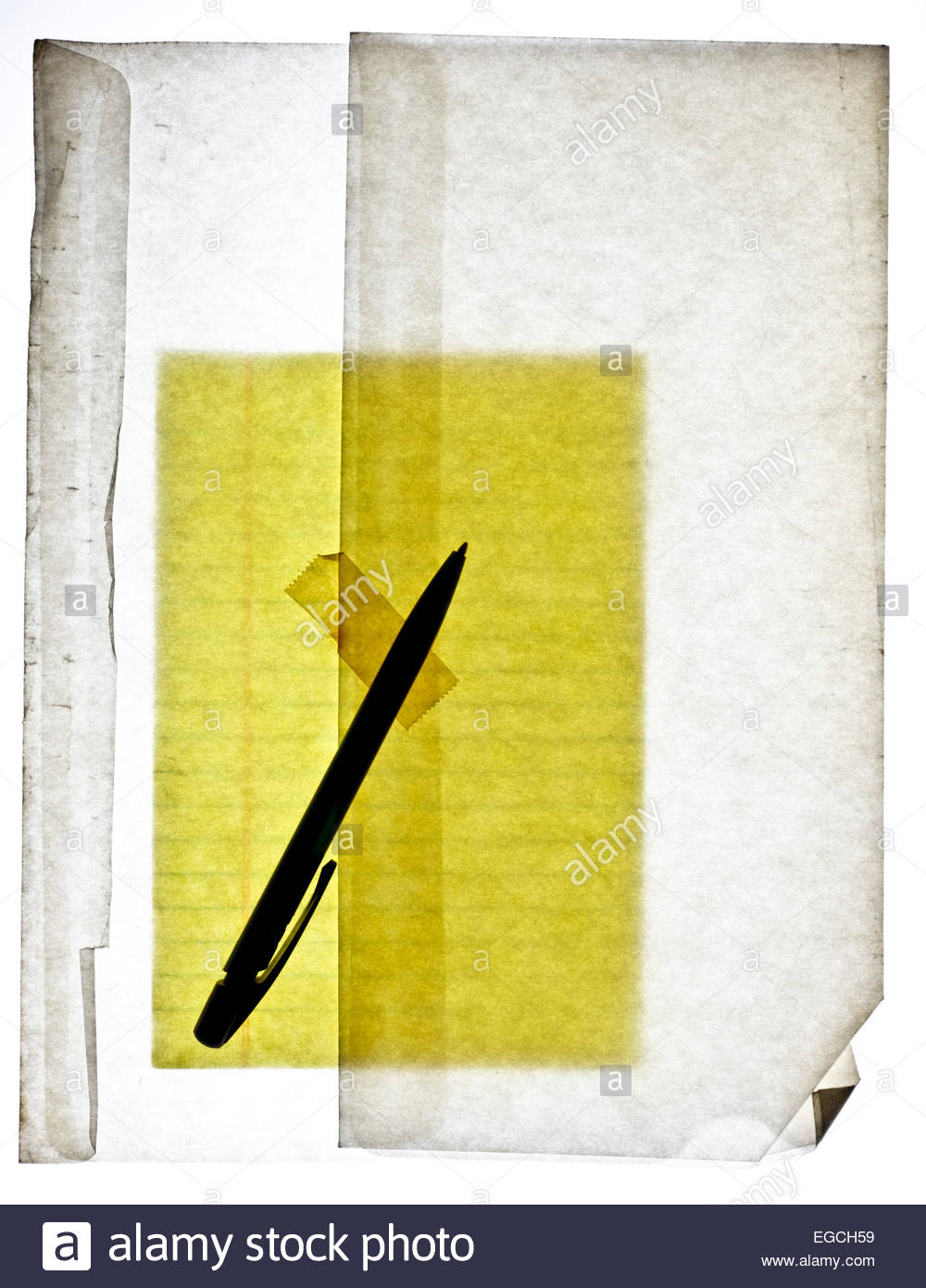 yellow lined notepad paper in translucent envelope with pen - Stock Image