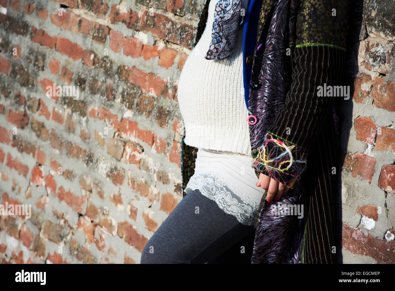 Pregnant woman standing leaned on a brick wall in outdoors - Stock Image