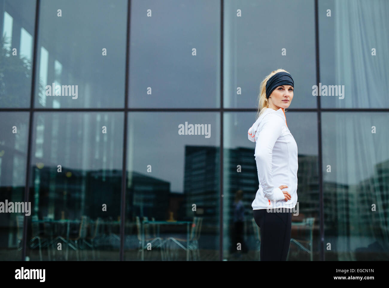 Portrait of confident young woman standing with her hands on hips looking at camera. Fitness model outdoors. - Stock Image