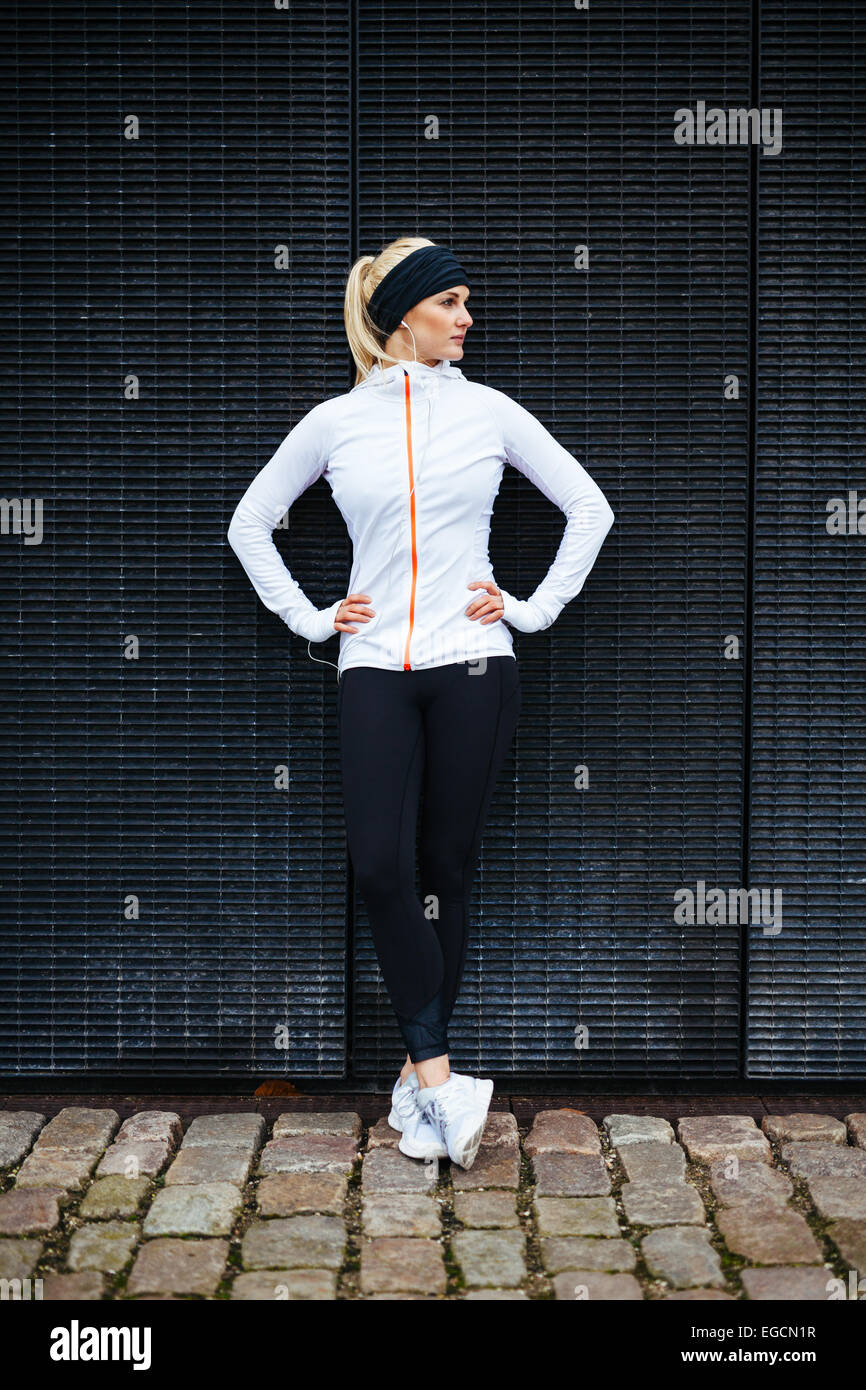 Full length shot of sporty young woman relaxing after running exercise. Female athlete resting after jogging in - Stock Image