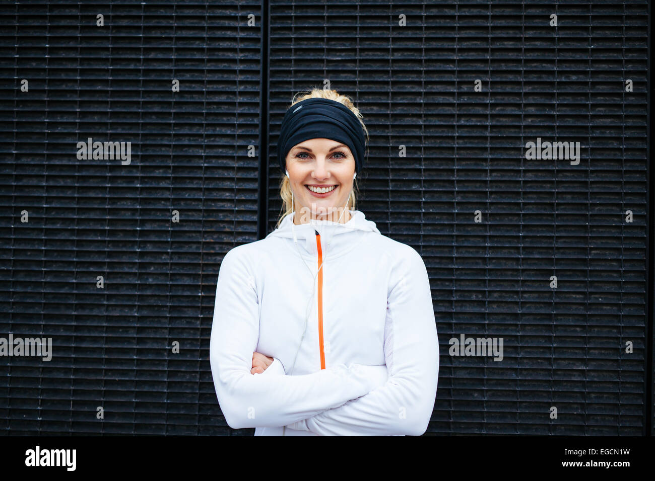 Portrait of happy young woman in sportswear looking at camera smiling. Fitness female against dark wall. - Stock Image