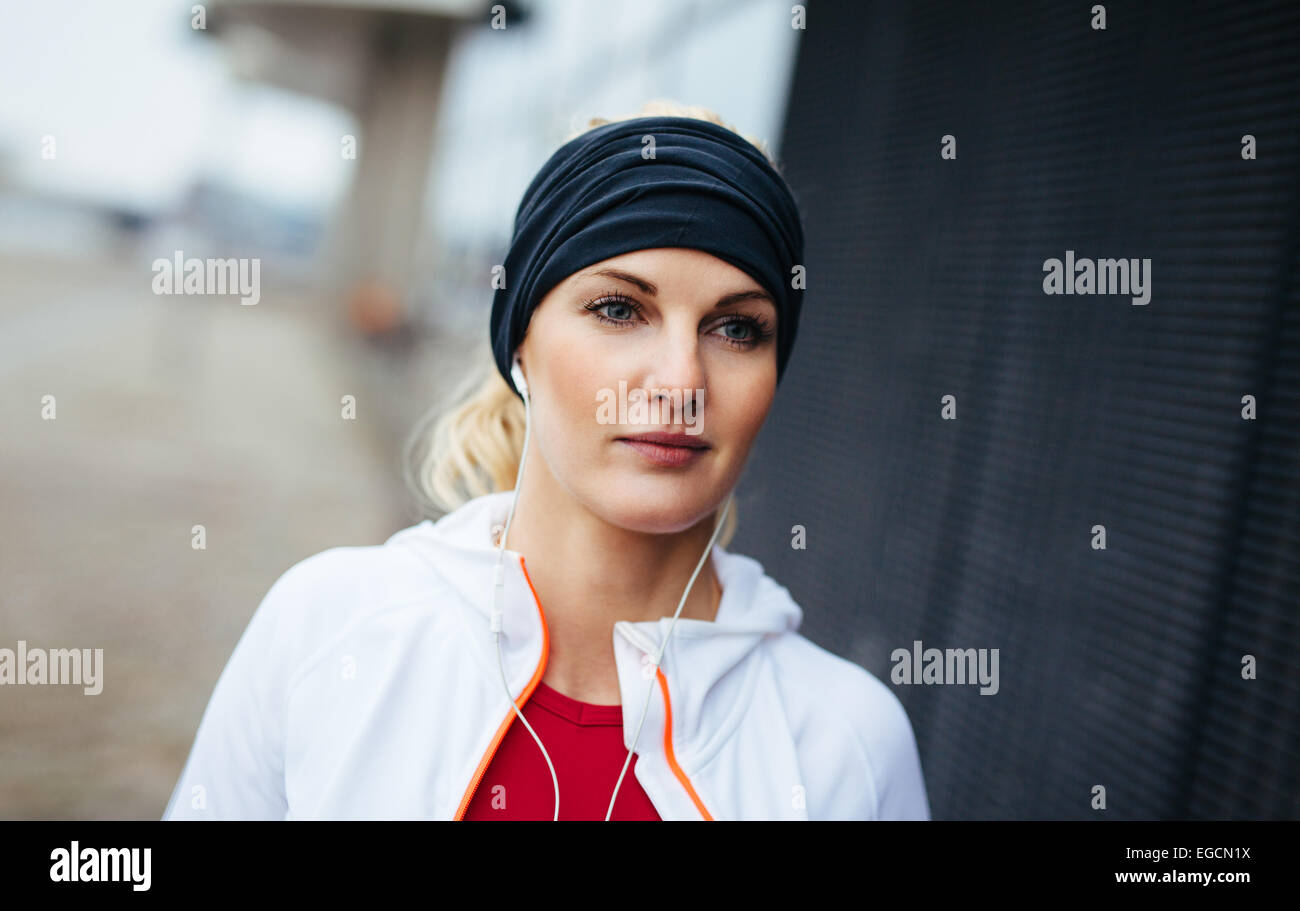 Close-up portrait of attractive and sport woman wearing headband and listening to music on earphones. Fitness female. - Stock Image