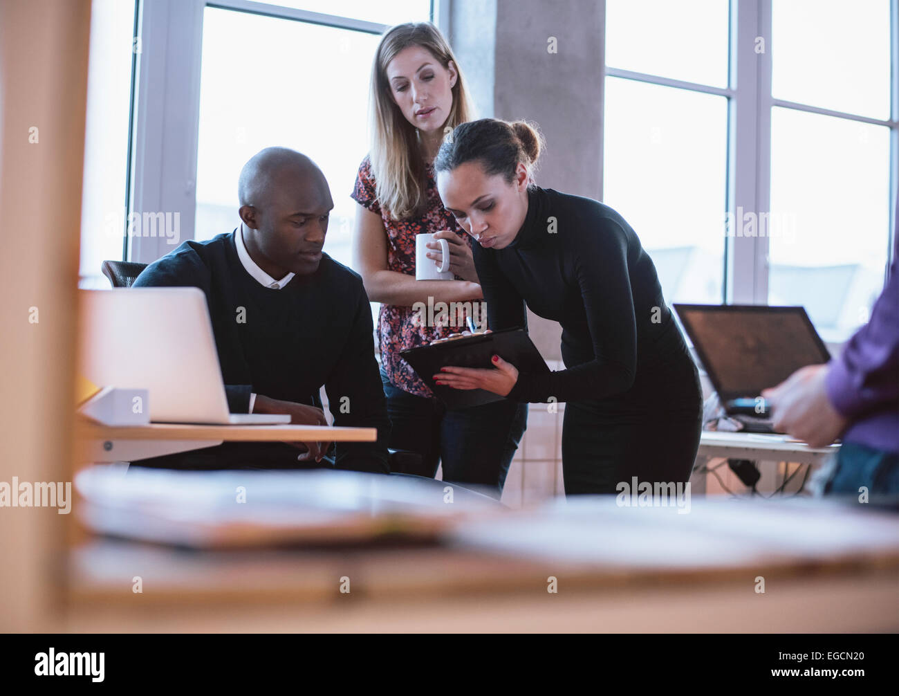 Female executive showing proposal on clipboard to her colleagues. Multiracial young people analyzing new business - Stock Image