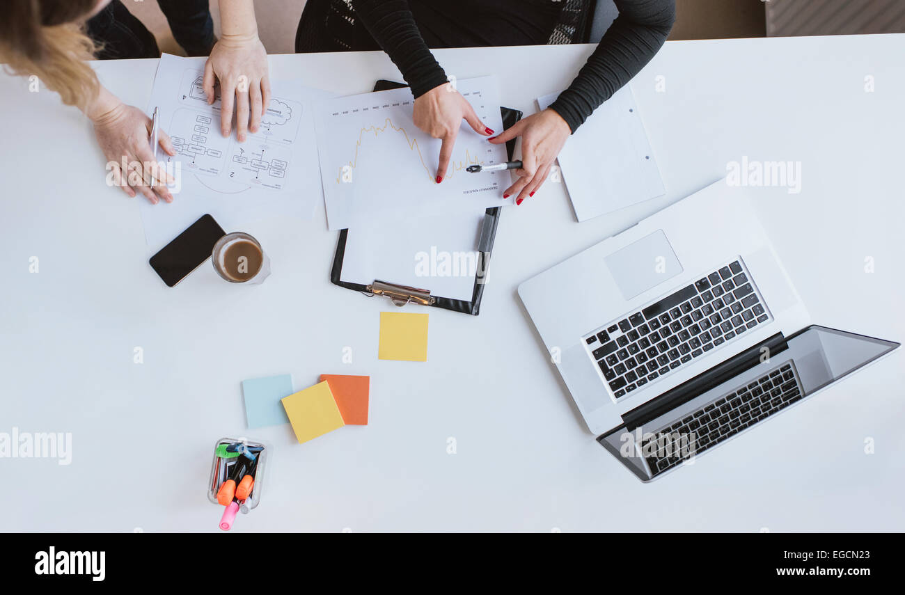 Top view of hands of two business woman analyzing financial data. Coworkers working on chart at desk in office. - Stock Image
