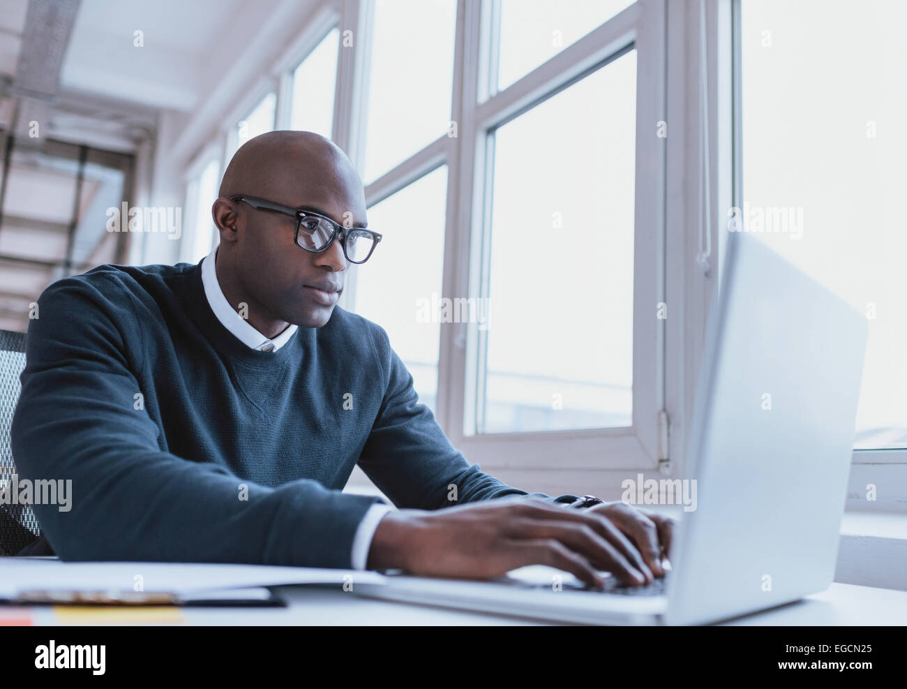 Image of african american businessman working on his laptop. Handsome young man at his desk. - Stock Image