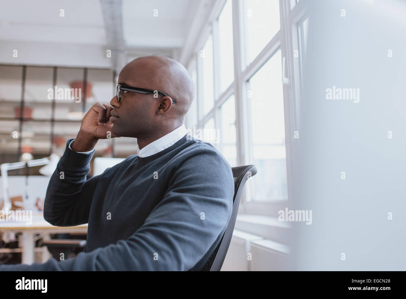 Side view of african executive sitting at his desk using mobile phone. Young man at work answering a phone call. - Stock Image