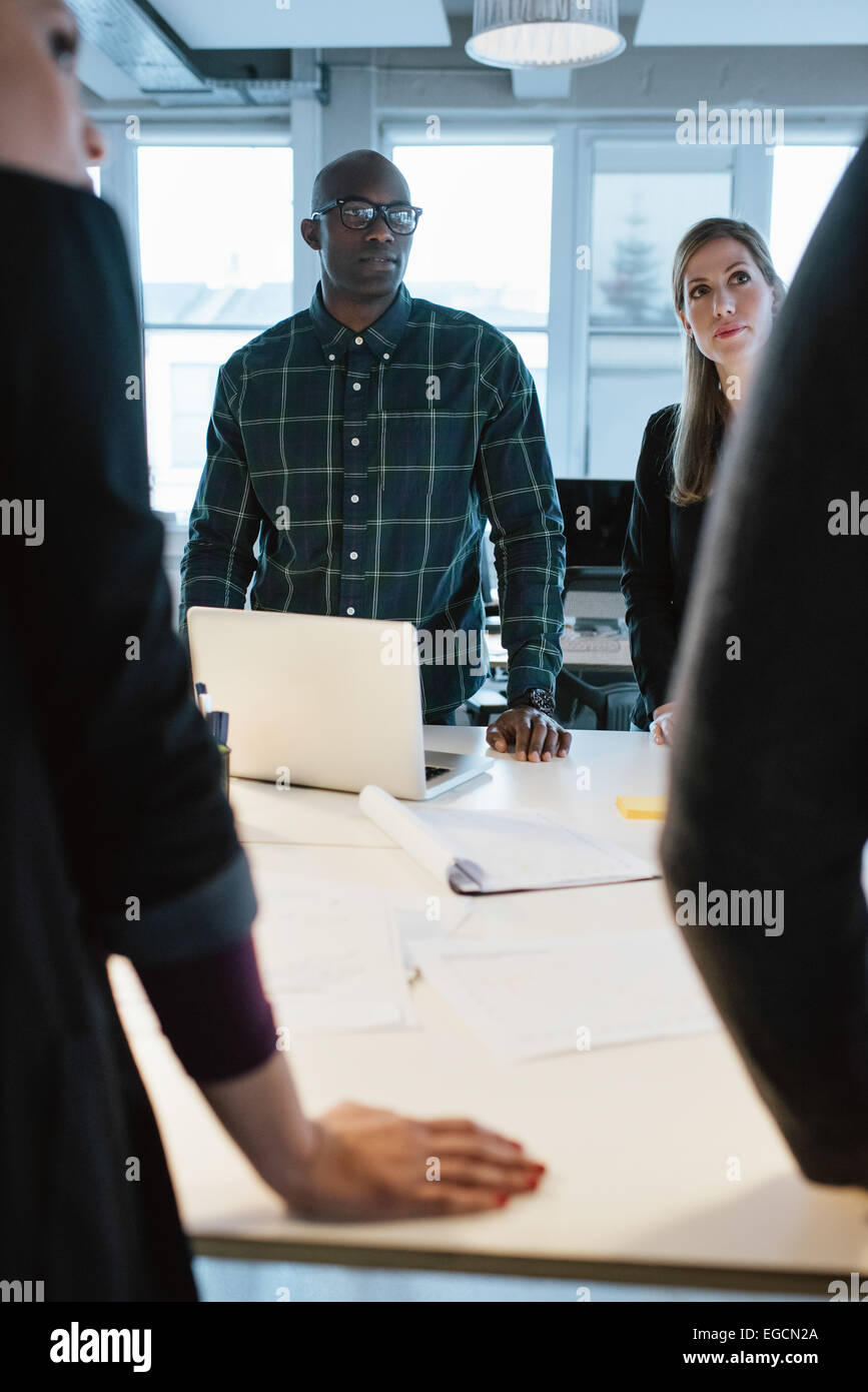 Young people standing at a table discussing work. African man with caucasian woman in office during meeting. - Stock Image