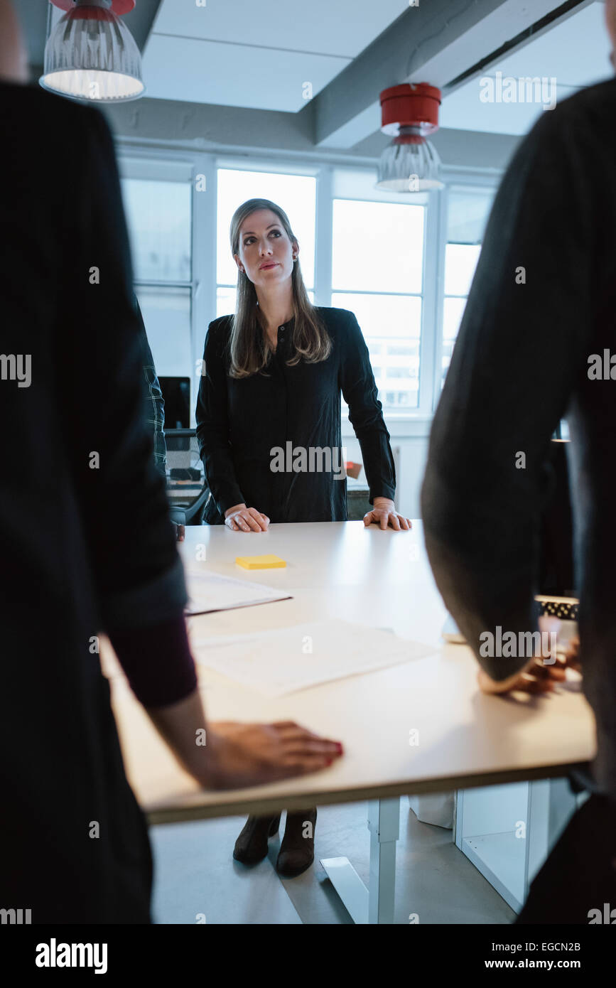 Young female executive with colleagues around a table at office. Business people during meeting. - Stock Image