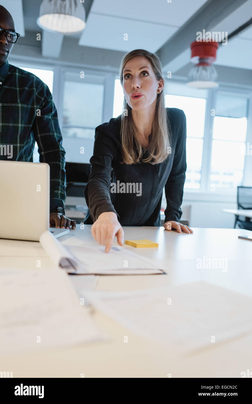 Female executive explaining business plan to her team in a meeting. Woman showing a document a colleagues at office. - Stock Image