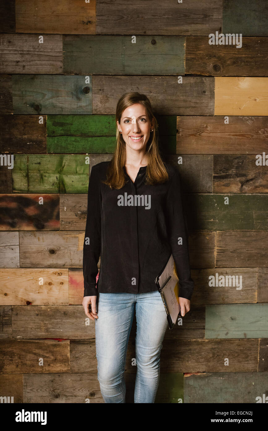 Portrait of young woman looking happy while posing for camera against a wooden wall in office. Young business executive - Stock Image