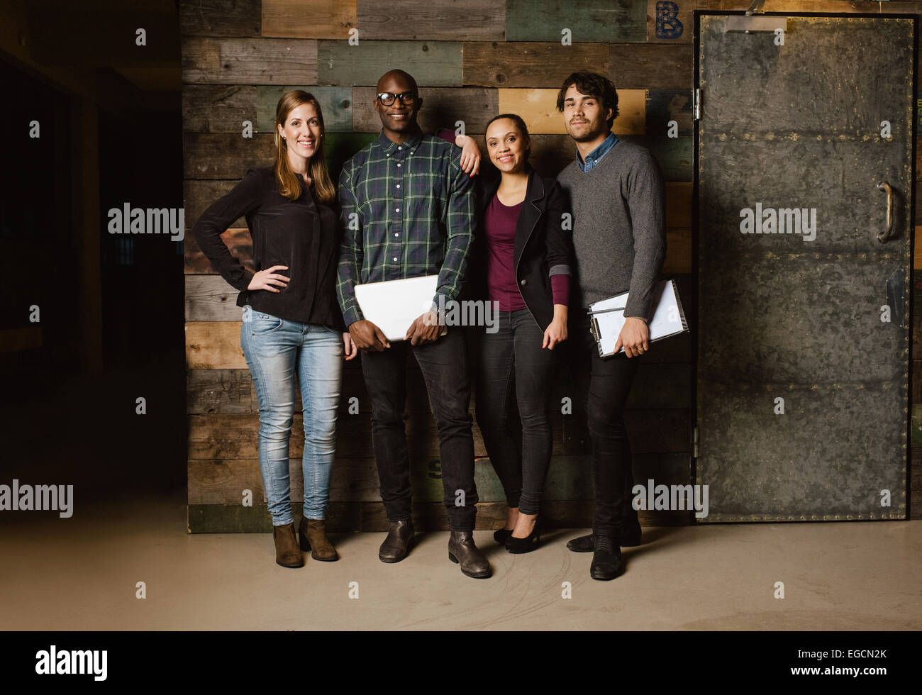 Portrait of successful business team standing together against wooden wall. Full length image of a group of diverse - Stock Image