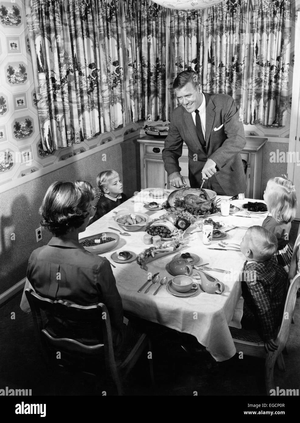 1950s FAMILY OF 5 THANKSGIVING HOLIDAY MEAL MOM DAD MAN WOMAN 3 KIDS BOYS GIRLS AT DINING ROOM TABLE FATHER CARVING - Stock Image