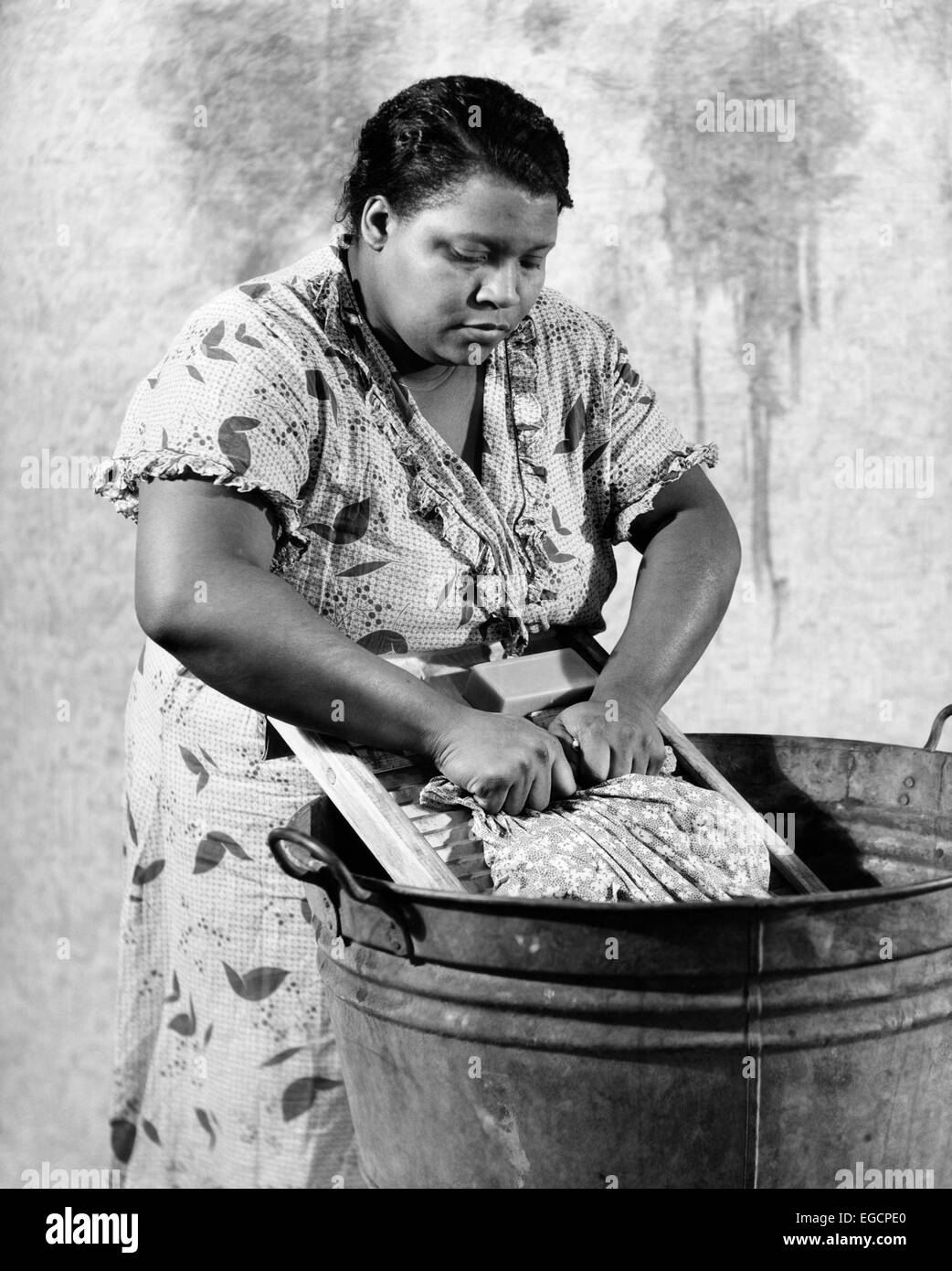 1930s AFRICAN-AMERICAN WOMAN WASHING SCRUBBING CLOTHES ON WASHBOARD IN A GALVANIZED ZINC WASHTUB - Stock Image
